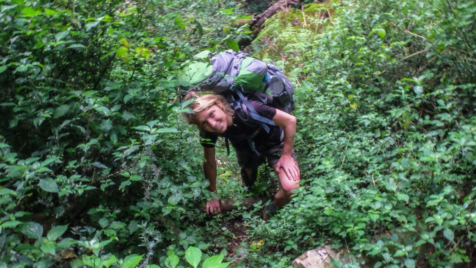 a photo of a hiker climbing a steep slope on the amathole trail.