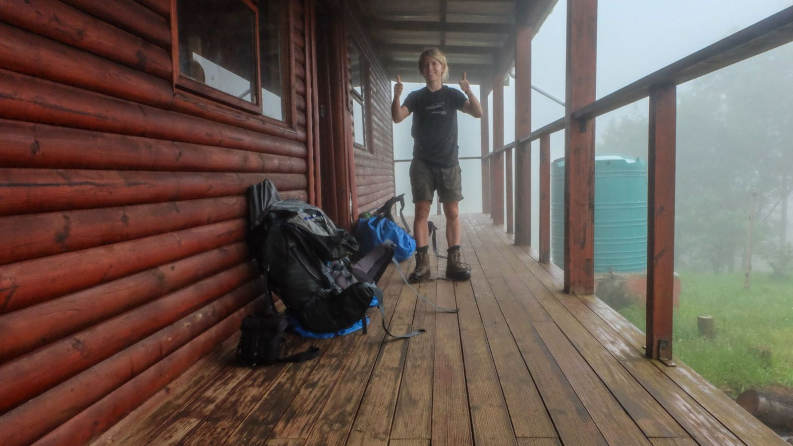 a photo of a hiker in front of a overnight hut on the amathole trail.