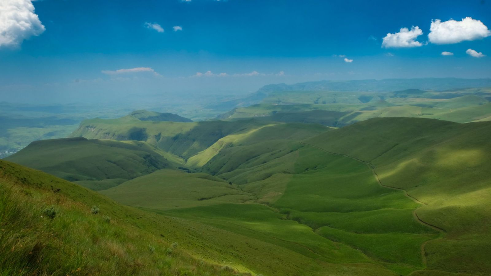 photo from the top showing a green valley in the drakensberg mountains