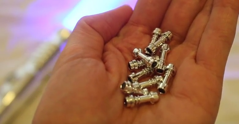 handful of small LEGO lightsabers with a chrome silver hilt