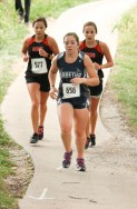 Senior Hunter Lowdermilk stays ahead of these two ACCHS runners during the girls' cross country race on Thursday, October 4, at the Sabetha Golf and Country Club.