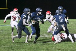 Junior linebacker Gabe Garber, left, and senior cornerback Mason Spellmeier, right, provide downfield blocking on this interception by senior defensive back Braeden Cox, who went 70 yards for the touchdown on Friday, October 12, against Wamego.