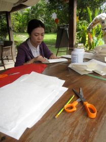 Katmanee making paper gift bags for Silk Worm Poo Tea at the LCC.