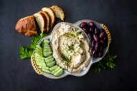 Mutabal recipe on mezze platter with olives, cucumber and bread