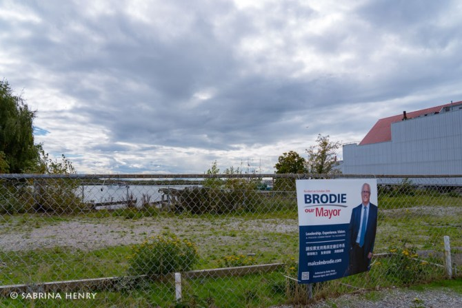 Political sign hangs on fence surrounding an empty site on Bayview in Steveston Village