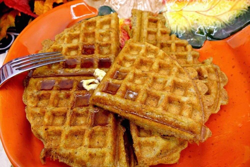 A section of homemade Paleo pumpkin waffles atop more Paleo pumpkin waffles, drizzled with maple syrup and grass-fed butter