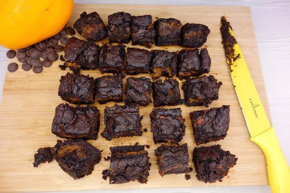 Homemade fudgy Paleo pumpkin swirl brownies aligned evenly on a wood cutting board with a sharp yellow knife and pumpkin surrounded by chocolate chips on the sides
