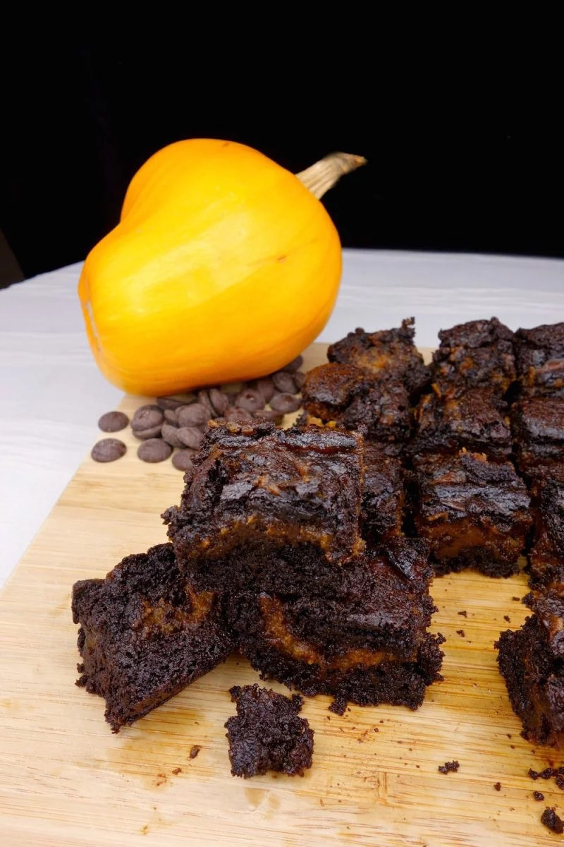 A stack of homemade fudgy Paleo pumpkin swirl brownies with more brownies in the background, alongside a pumpkin surrounded by chocolate chips