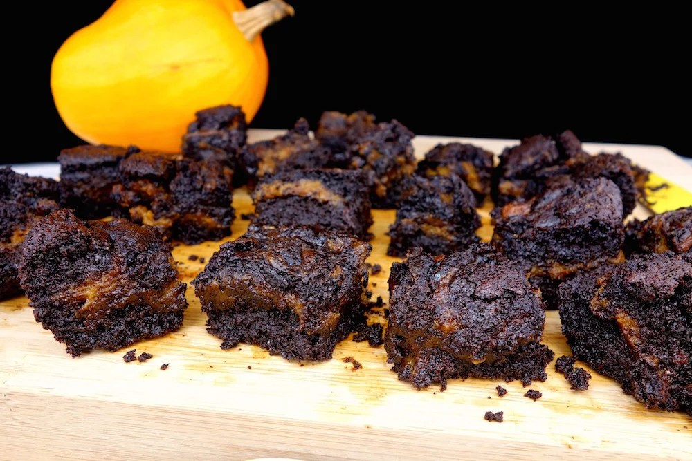 Rows of homemade fudgy Paleo pumpkin swirl brownies on a wood cutting board with a pumpkin in the distance