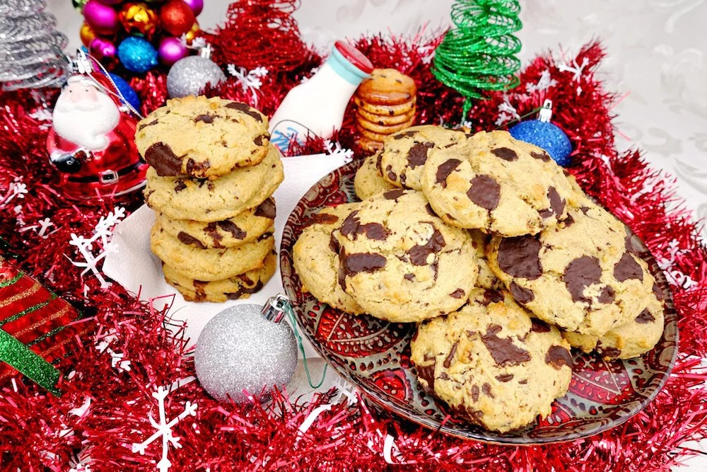 Homemade soft and chewy Paleo chocolate chip cookies stacked and on a plate, surrounded by red garland and Christmas decorations