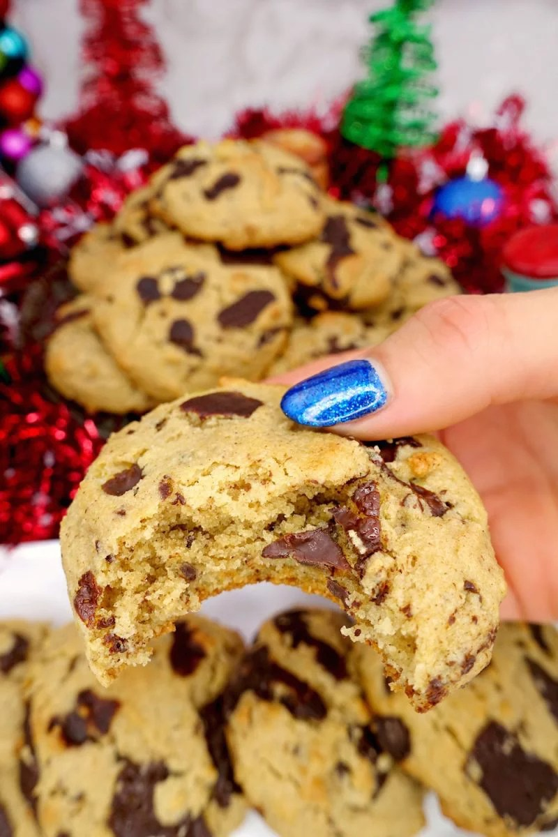 a hand holding a homemade soft and chewy Paleo chocolate chip cookie with bite taken out of it with more cookies and Christmas decoration in the background