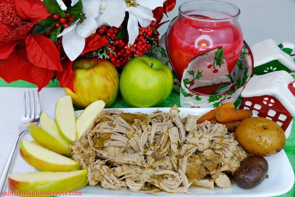 Shredded Slow-Cooker Paleo Apple Pork Tenderloin on a white dish with a side of slice granny smith apple and baby carrots and potatoes, with two apples, a red candle, Christmas ribbon, and festive flowers in the background