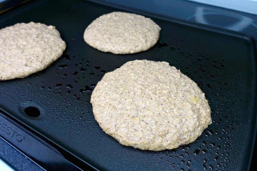 Homemade healthy gluten-free greek yogurt oat pancake batter freshly poured on a black electric griddle