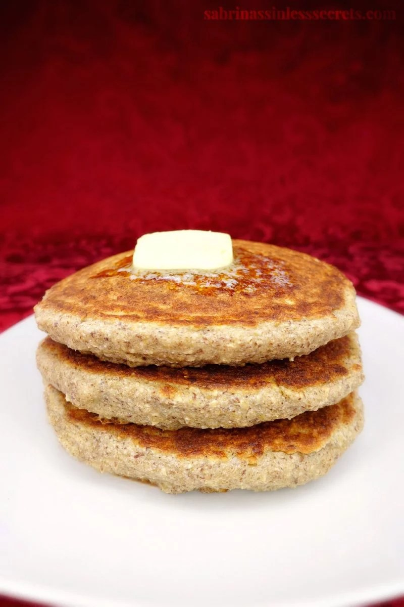 A stack of freshly made healthy gluten-free greek yogurt oat pancakes on a white plate with a slice of melty butter on top