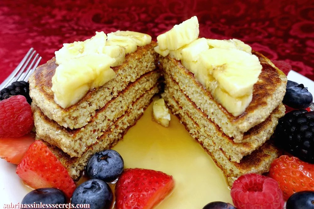 Healthy homemade gluten-free greek yogurt oat pancakes cut down the middle on a white plate, with banana slices on top and berries and maple syrup on the plate