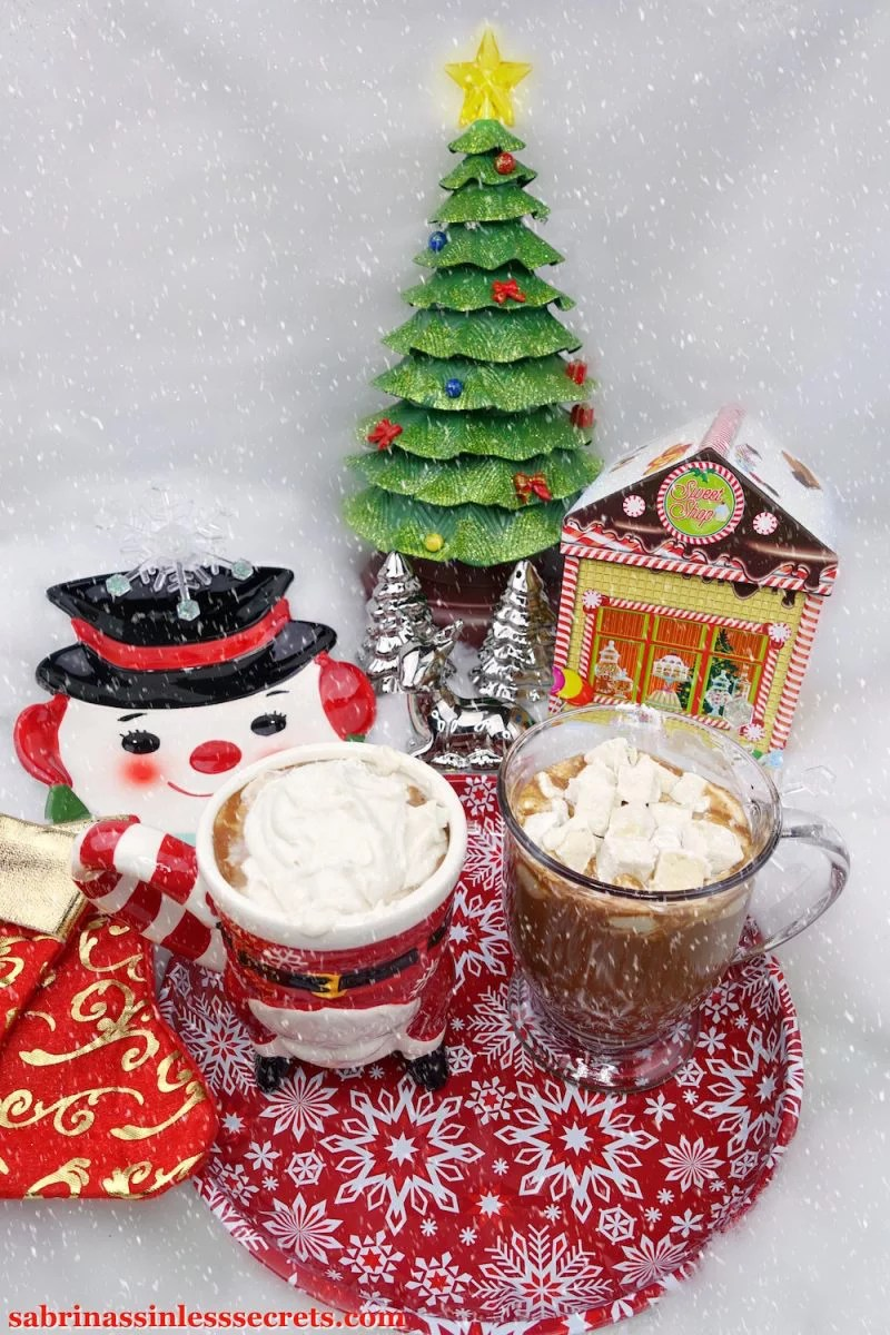 Two mugs of Paleo hot chocolate, one with Paleo whipped cream on top and the other, Paleo marshmallows, sitting on top of a red and white snowflake plate with Christmas decor surrounding and falling snow
