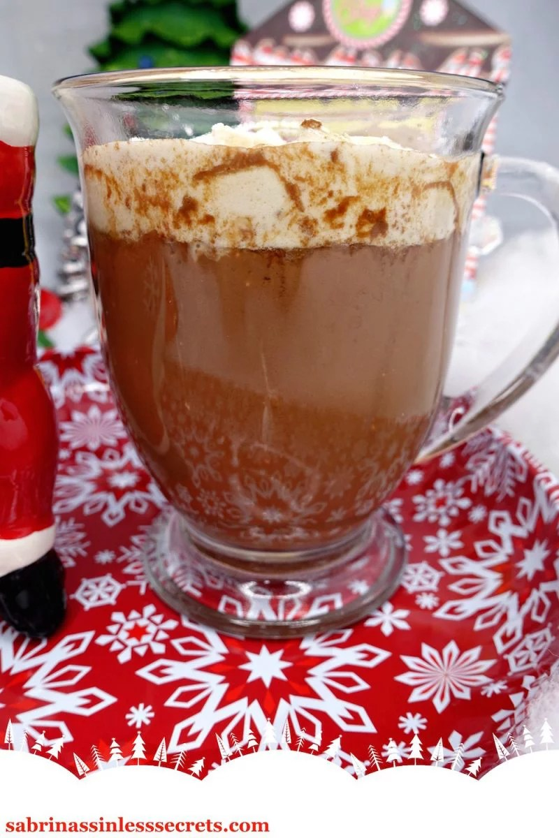 A clear mug full of Paleo hot chocolate with melty homemade Paleo marshmallows on top, resting on a red and white snowflake plate