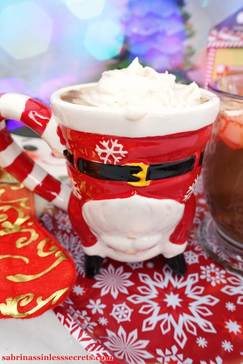 Paleo hot chocolate in a santa mug with Paleo whipped cream on top, resting on top of a red and white snowflake plate