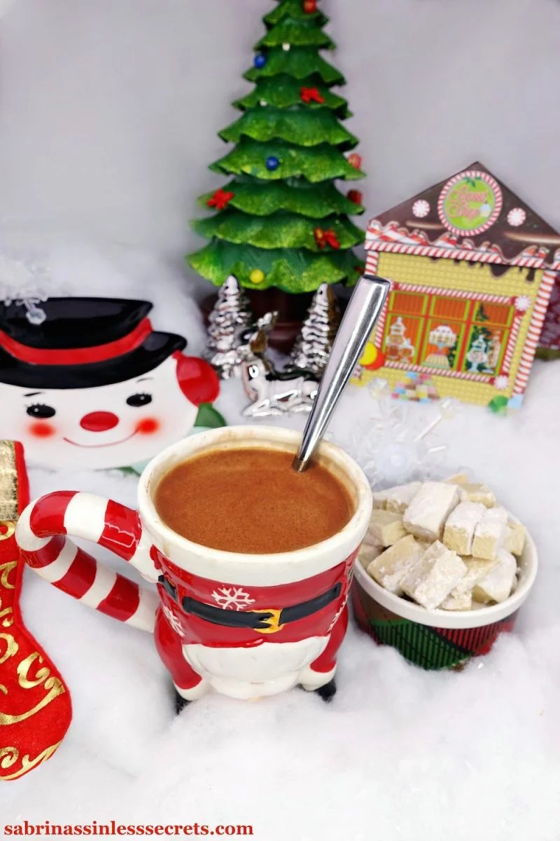 Paleo hot chocolate in a santa mug, resting on top of fluffy snow with a cup of homemade Paleo marshmallows next to it, along with other Christmas decorations