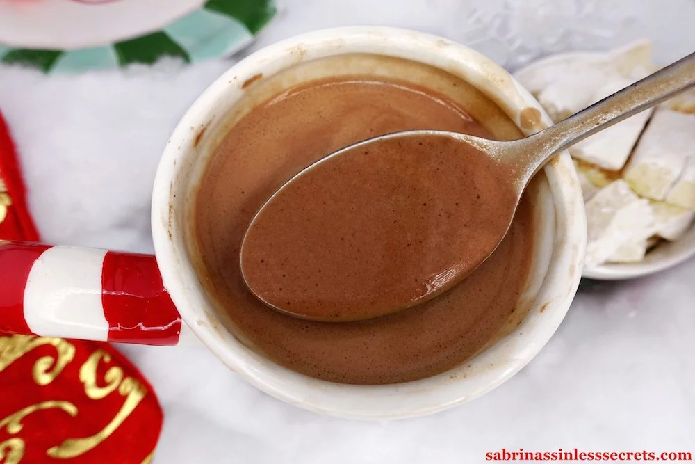 An up-close image of a spoonful of Paleo hot chocolate hovering over santa mug full with hot chocolate