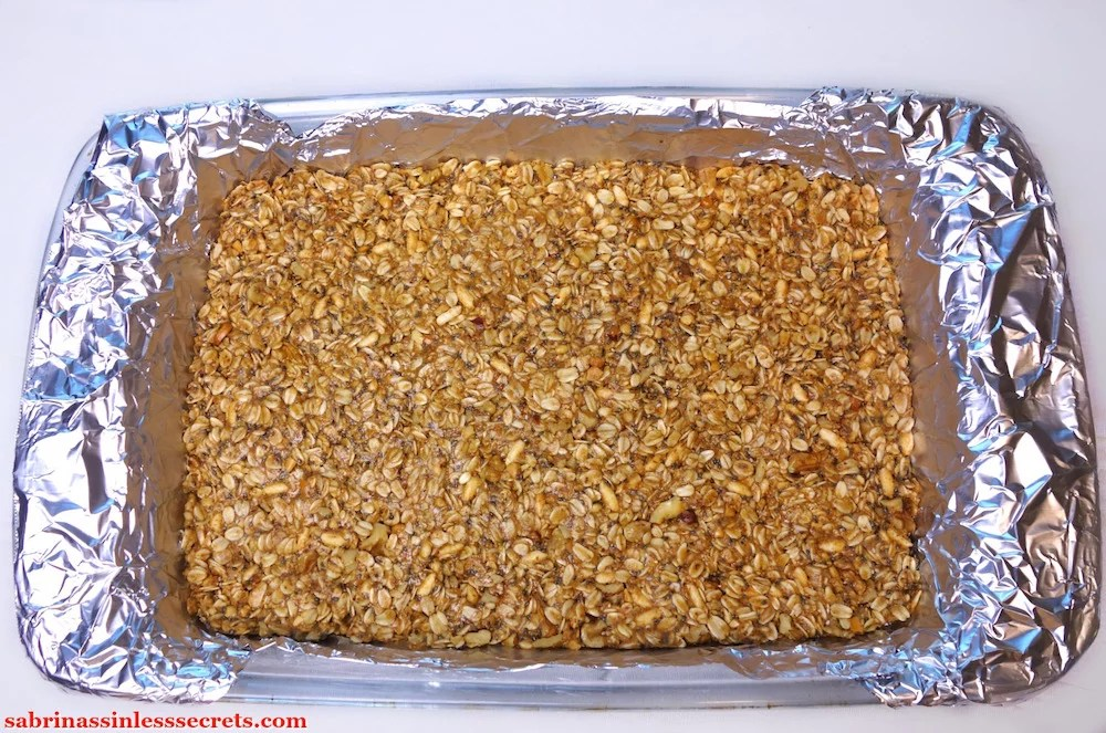 The base of the Gluten-Free Triple Peanut Butter Granola Bars after being firmly pressed in a foil-lined 9x13-inch pyrex dish
