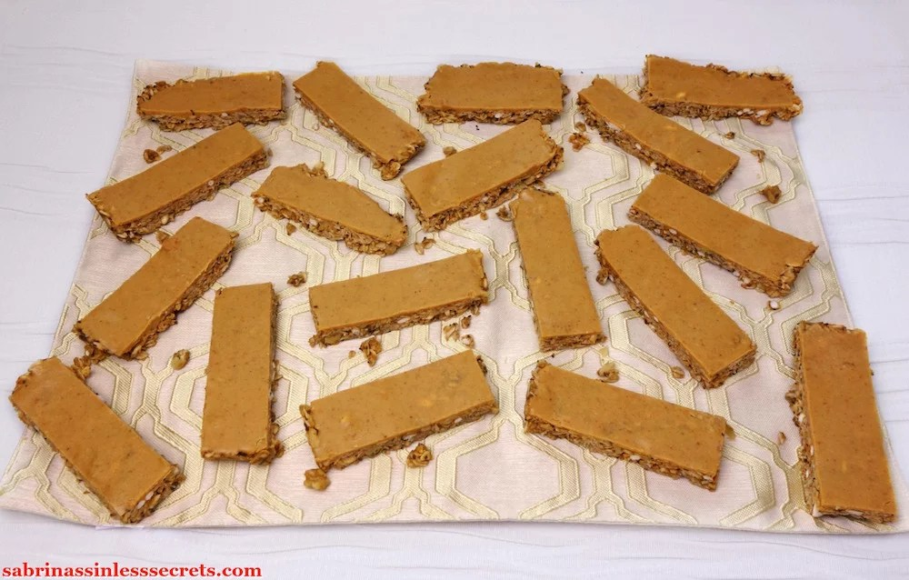 An arrangement of Gluten-Free Triple Peanut Butter Granola Bars on a tannish placemat