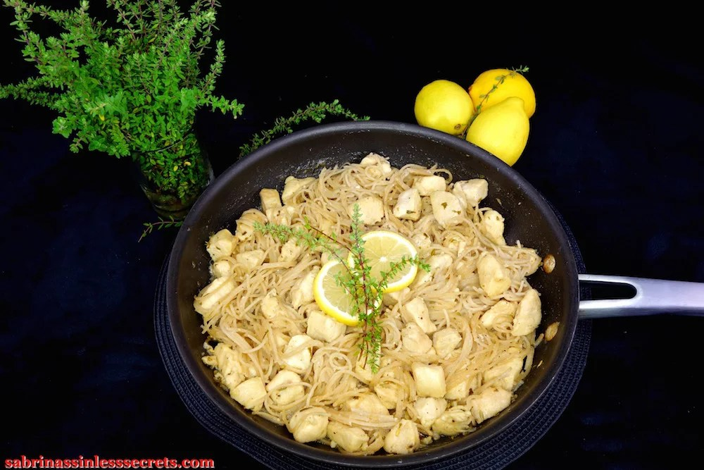 Lemon Thyme Honey Chicken with Angel Hair Pasta on a dark non-stick large skillet, with garnishes of sliced lemon and springs of lemon thyme in the center—sitting on a black background with lemons and lemon thyme on the sides