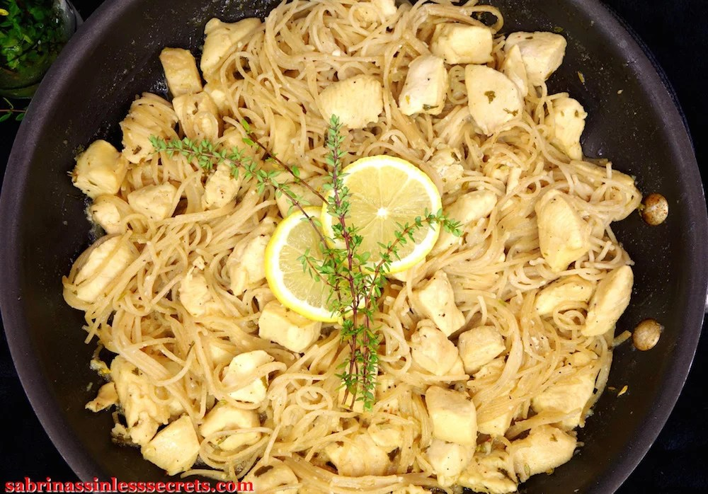 A close up image of Lemon Thyme Honey Chicken with Angel Hair Pasta in a large dark non-stick skillet, garnished with fresh lemon slices and lemon thyme springs