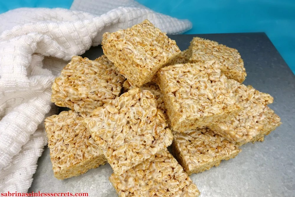 A pile of Healthy Brown Rice Crispy Treats made with Paleo marshmallows on a silver platform with a white towel