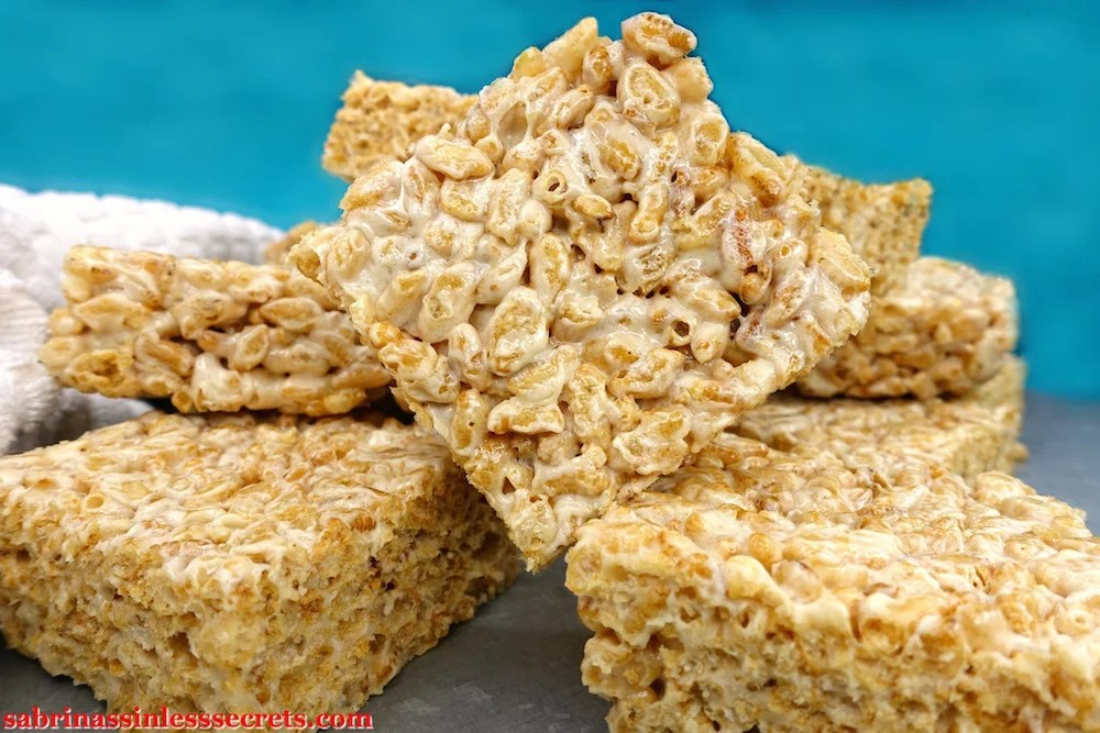 a diagonal Healthy Brown Rice Crispy Treat made with Paleo marshmallows on top of other healthy brown rice crispy treats with a blue background