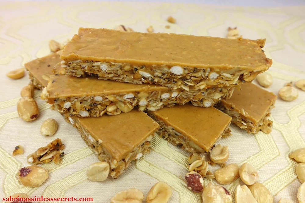 four Gluten-Free Triple Peanut Butter Granola Bars arranged criss cross on each other with nuts around them