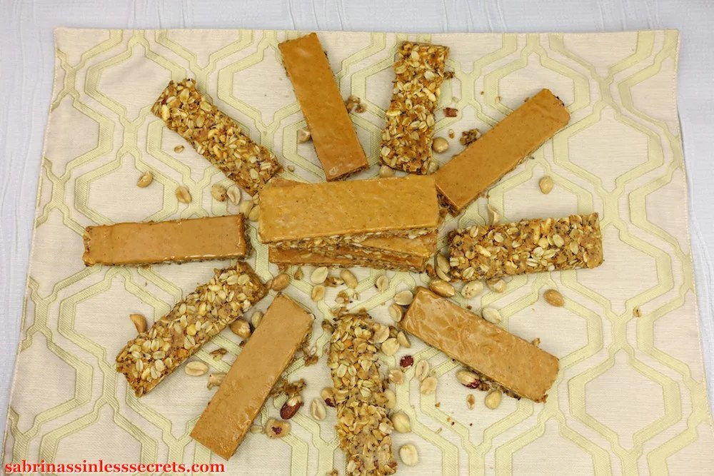 An overhead view of stacked Gluten-Free Triple Peanut Butter Granola Bars with more Gluten-Free Triple Peanut Butter Granola Bars circling them, some turned over on a tannish placemat