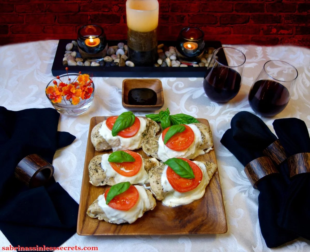 Five homemade Chicken Caprese chicken breasts on a wood square plate, a side of balsamic reduction, black cloth napkins, two glasses of red wine, cancels, and a bowl of red and orange flowers resting on a white tablecloth and in front of a red brick background
