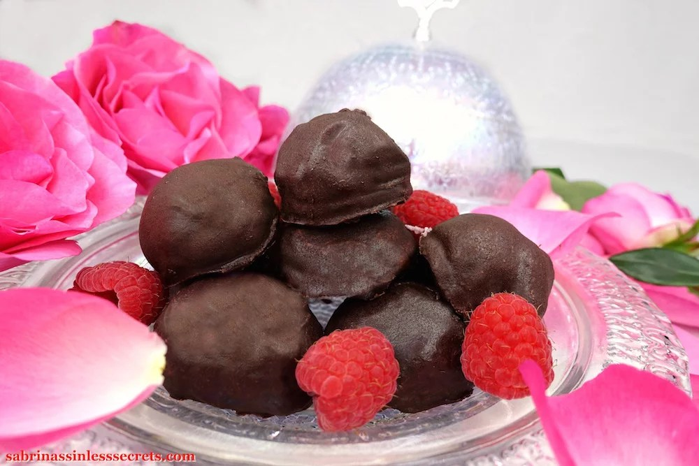 Homemade dark chocolate ball-shaped Paleo Raspberry Cream Truffles sitting on a pearlescent plate with fresh raspberries and pink roses