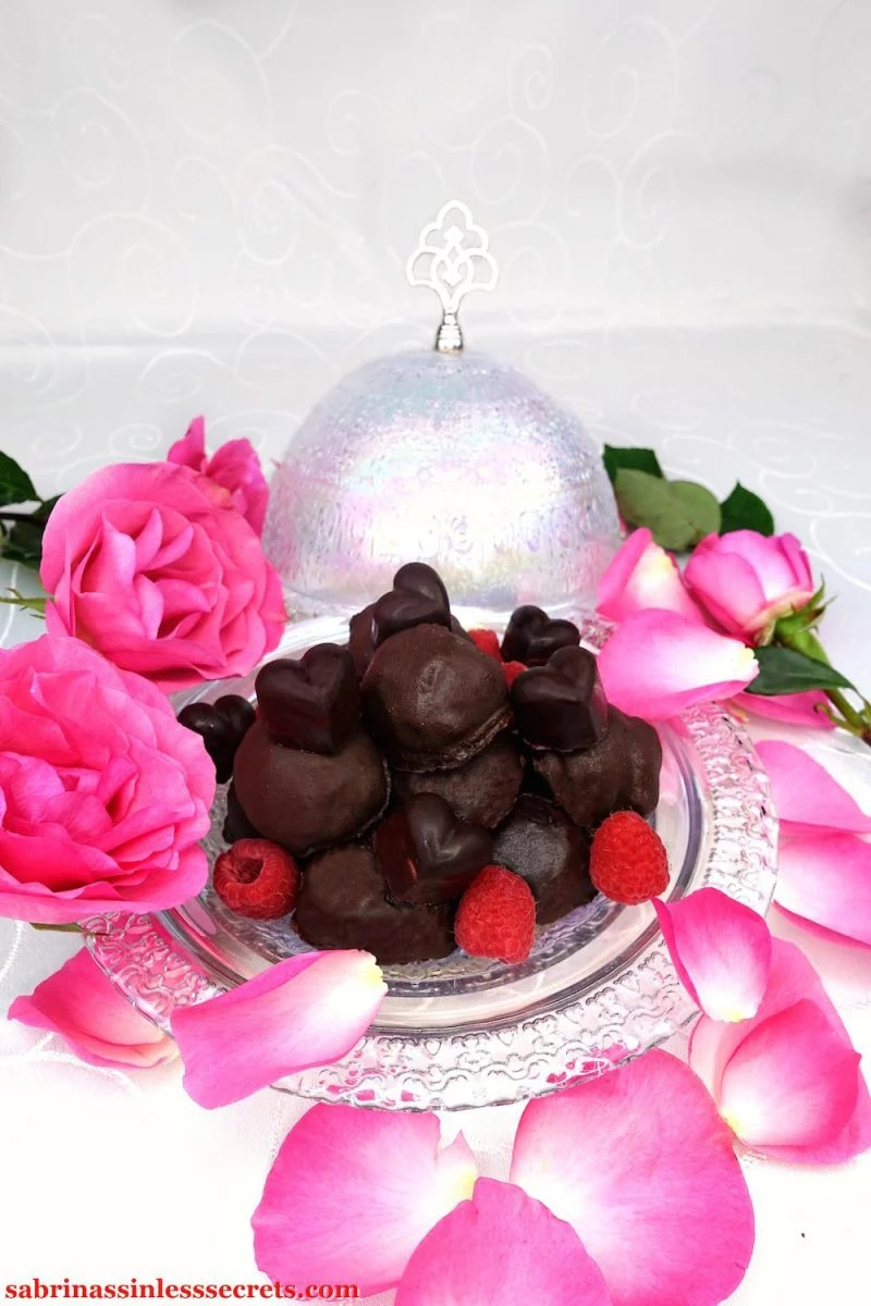 Homemade heart and ball-shaped dark chocolate Paleo Raspberry Cream Truffles piled atop each other with fresh raspberries scattered throughout, and fresh pink roses and rose petals surrounding them on a white tablecloth