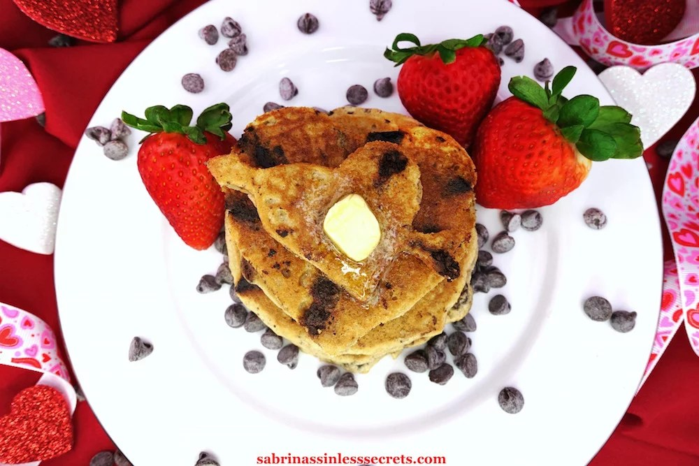homemade Paleo Dark Chocolate Chip Pancakes topped with melty grass-fed butter on a white plate with fresh strawberries on the side and scatters of chocolate chips,