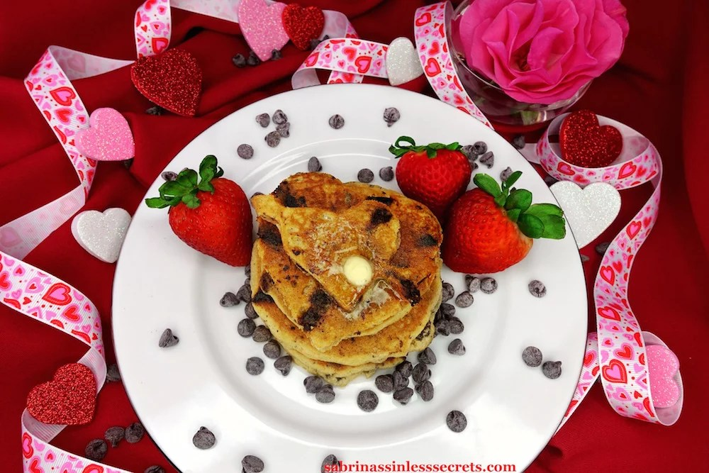 homemade Paleo Dark Chocolate Chip Pancakes topped with melty grass-fed butter on a white plate with fresh strawberries on the side and scatters of chocolate chips, in addition to sparkly red, white, and pink hearts, heart ribbon, and red and pink roses in the background of red