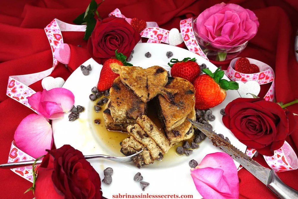 Homemade Paleo Dark Chocolate Chip Pancakes on a white plate cut in half with a generous bite on a fork resting in front of them, surrounded by maple syrup, chocolate chips, fresh strawberries, and red and pink rose petals, with red and pink roses, sparkly red, white, and pink hearts, and heart embellished ribbon in the background of red