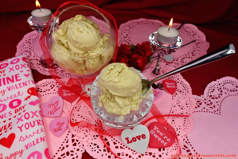 A chilled crystal bowl full of two scoops of Creamy Vanilla Bean Paleo Ice Cream with a spoon in it, with a glass stand-up bowl full of scoops of more ice cream in the background, resting atop pink paper hearts and encircled with red diaphanous ribbon, red carnations, and tea light candles atop crystal candles holders