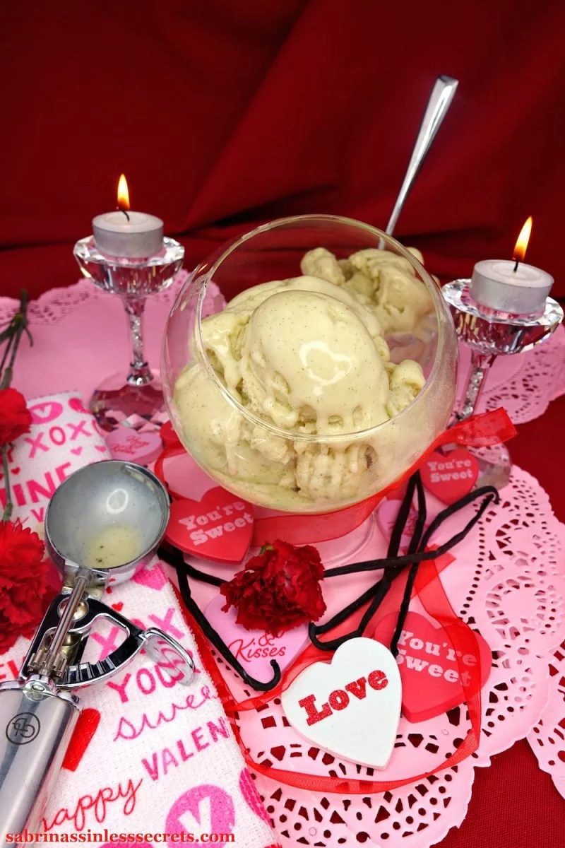 A bowl of melty Creamy Vanilla Bean Paleo Ice Cream scoops in a glass stand-up bowl, sitting atop pink paper hearts, surrounded by fresh vanilla beans, red carnations, heart messages, tea light candles atop crystal candle holders, and a used stainless steel ice cream scooper atop a Valentine's Day-inspired towel