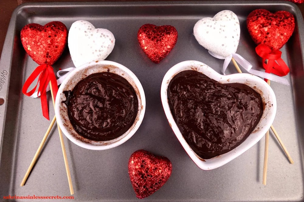 Two 6 oz. ramekins, one round and the other heart-shaped, filled with batter for Dark Chocolate Paleo Lava Cakes for Two on a cookie sheet with decorative, sparkly red and white hearts