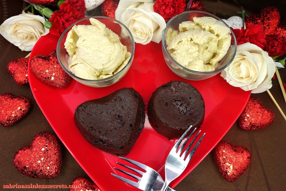 Two homemade Dark Chocolate Paleo Lava Cakes, one heart-shaped and one round, on a red heart-shaped plate, with two crossed stainless steel forks, two bowls of Creamy Vanilla Bean Paleo Ice Cream, glittery red hearts, white roses, and red carnatians atop a brown tablecloth