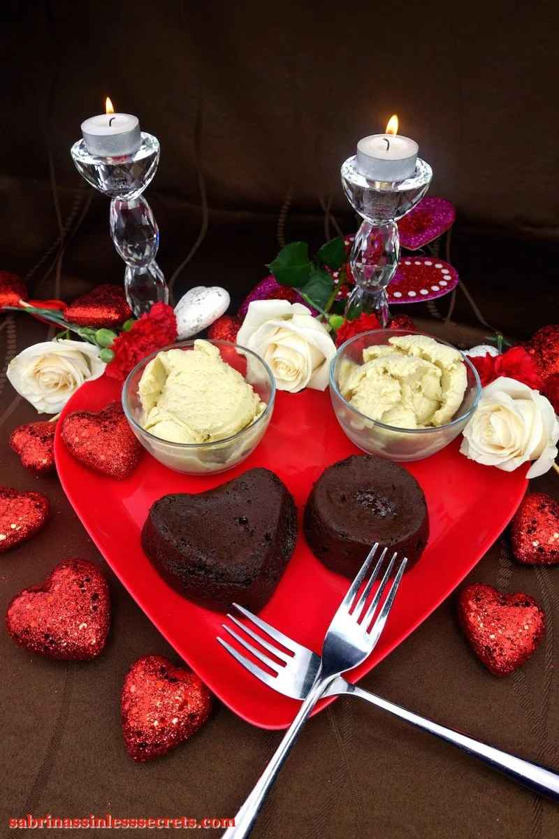 Two homemade Dark Chocolate Paleo Lava Cakes, one heart-shaped and one round, on a red heart-shaped plate, with two crossed stainless steel forks, two bowls of Creamy Vanilla Bean Paleo Ice Cream, glittery red hearts, white roses, red carnations, and two crystal candles holder with two white tea light candles atop a brown tablecloth