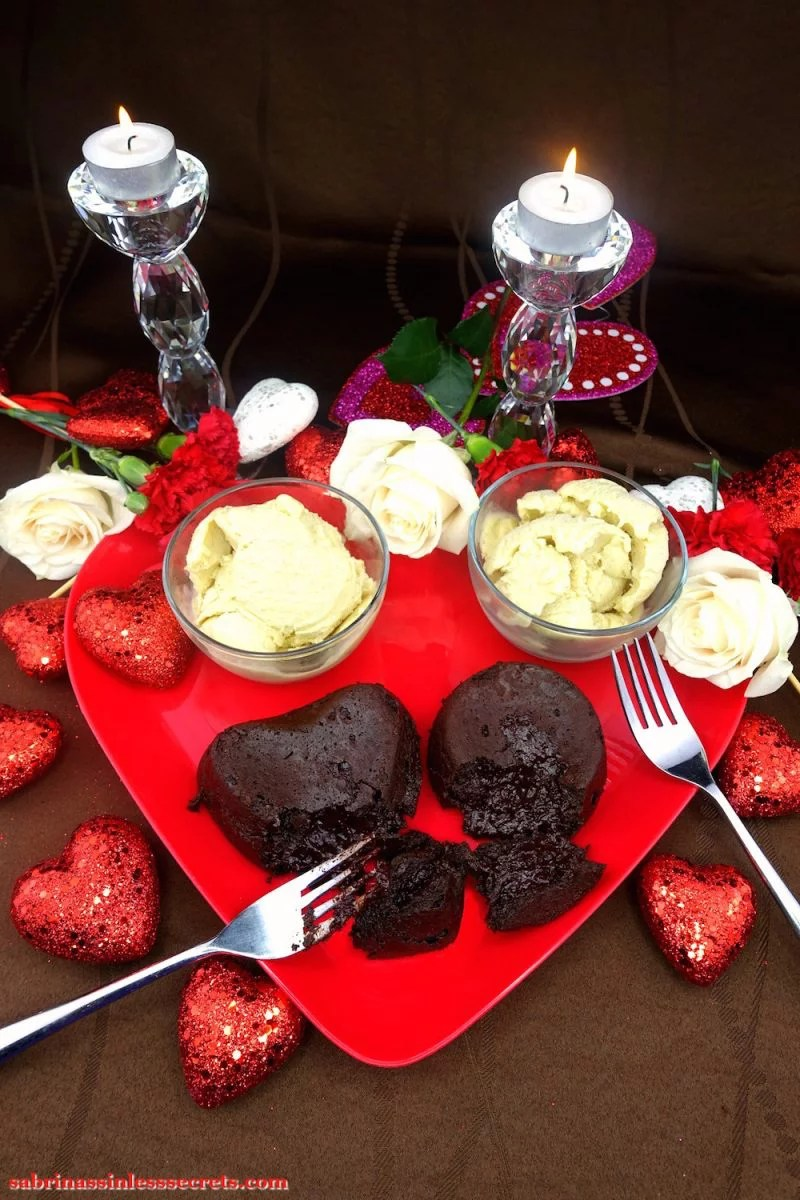 Two homemade broken Dark Chocolate Paleo Lava Cakes, one heart-shaped and one round, on a red heart-shaped plate, with two crossed stainless steel forks, two bowls of Creamy Vanilla Bean Paleo Ice Cream, glittery red hearts, white roses, red carnations, and two crystal candles holder with two white tea light candles atop a brown tablecloth
