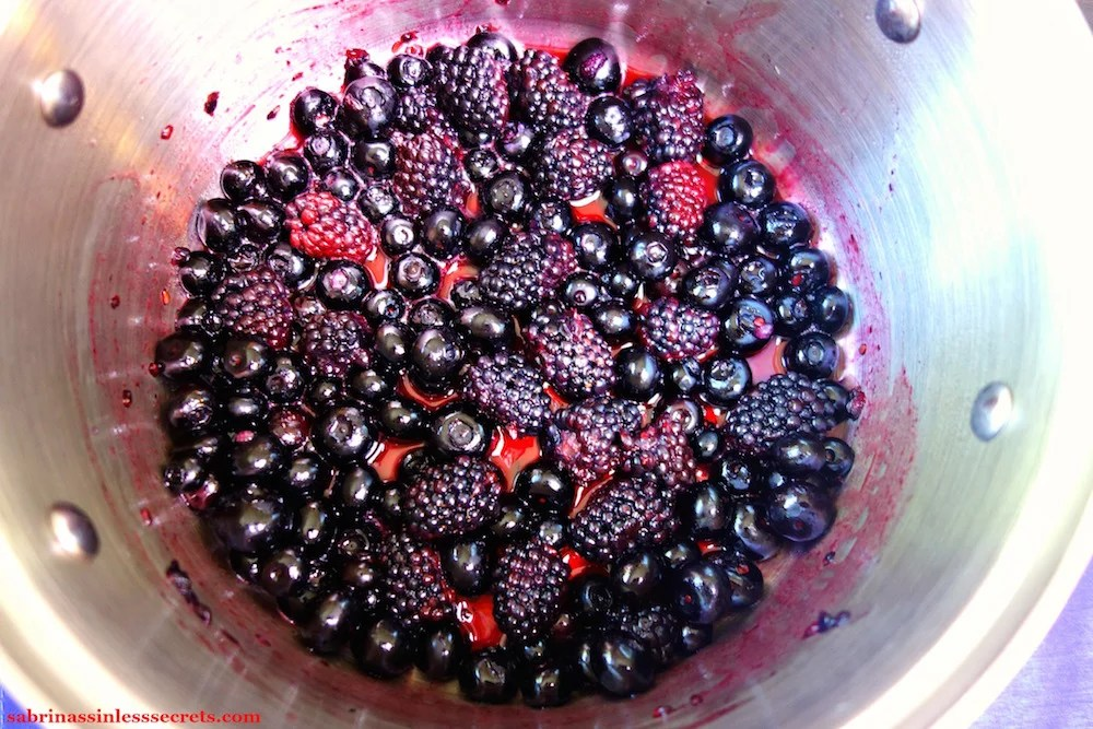 Fresh blueberries and blackberries in a stainless steel sauce pan being simmered