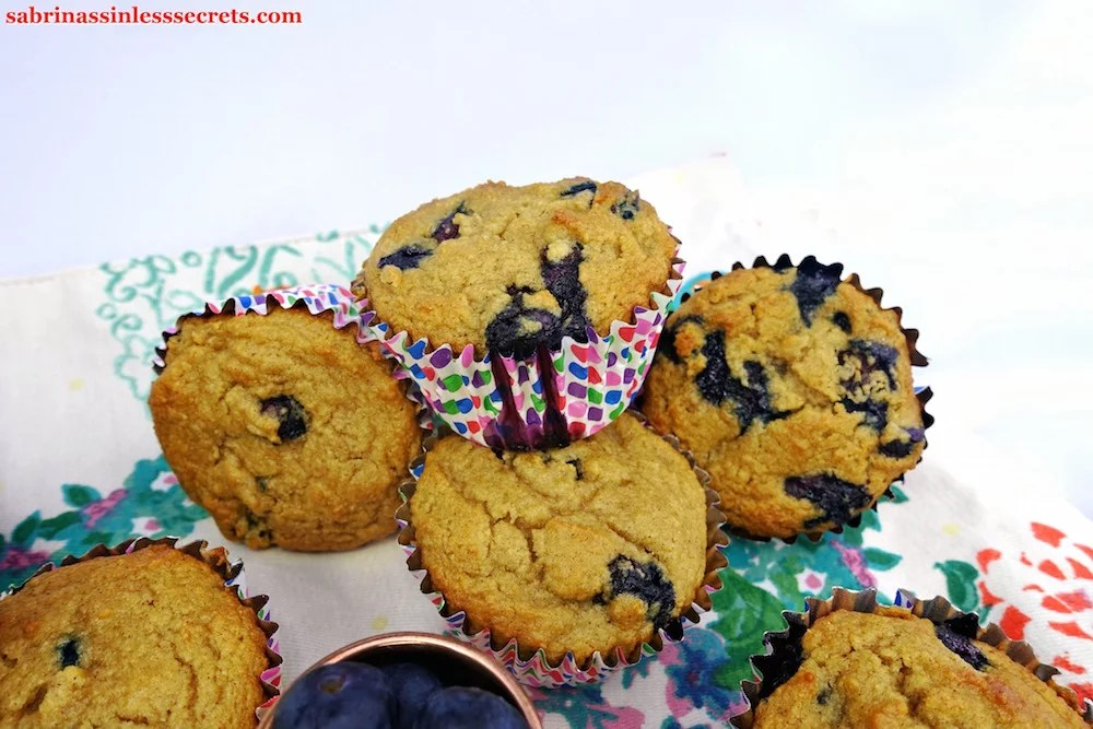 A mountain of four Apple Blueberry Paleo Muffins, the top one having blueberry sauce dripping over the side of the white liner with colorful dots
