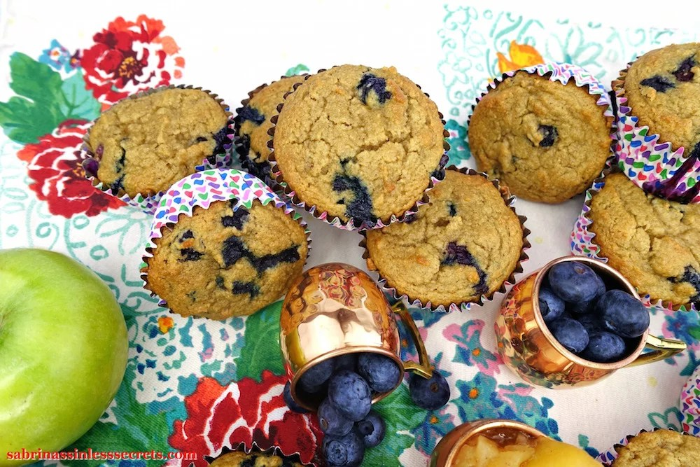 A mountain of homemade Apple Blueberry Paleo Muffins, joined by two petite copper mugs with fresh blueberries
