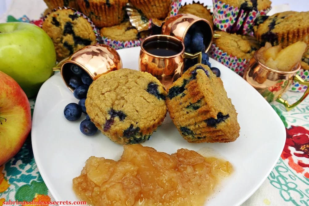 Two homemade Apple Blueberry Paleo Muffins on a white plate, accessorized with three peitite copper mugs, two turned over with fresh blueberries and one with hot, black coffee, in addition to a side of homemade Paleo chunky applesauce
