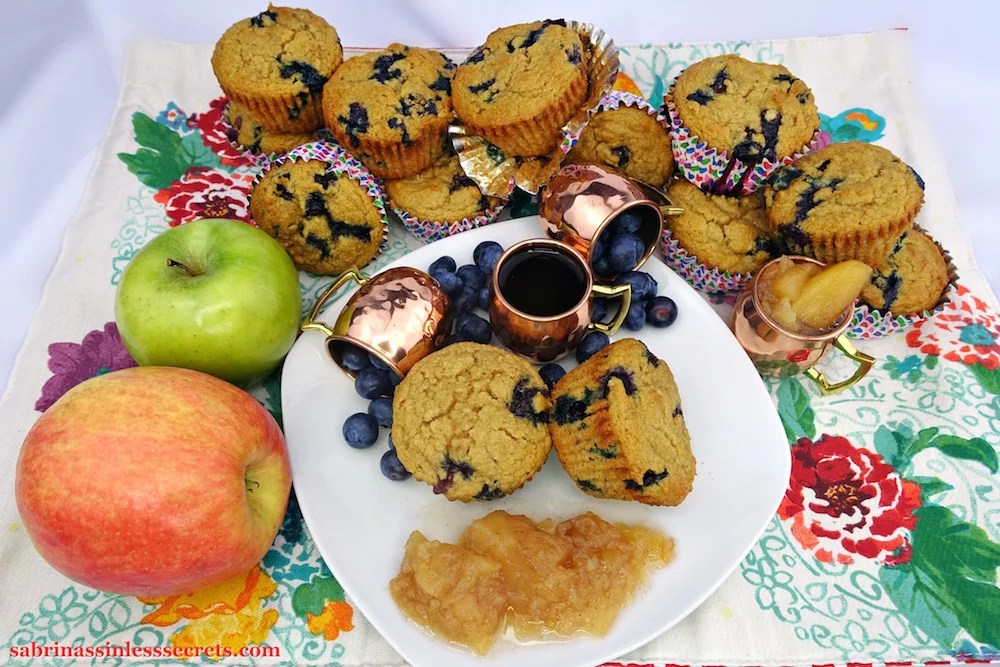Two homemade Apple Blueberry Paleo Muffins on a white plate, accessorized with three petite copper mugs, two turned over with fresh blueberries and one with hot, black coffee, in addition to a side of homemade Paleo chunky applesauce, resting on a colorful floral placement with additional muffins assorted on top of one another in the background with another small copper mug full of applesauce and one granny smith apple and one honey crisp apple.