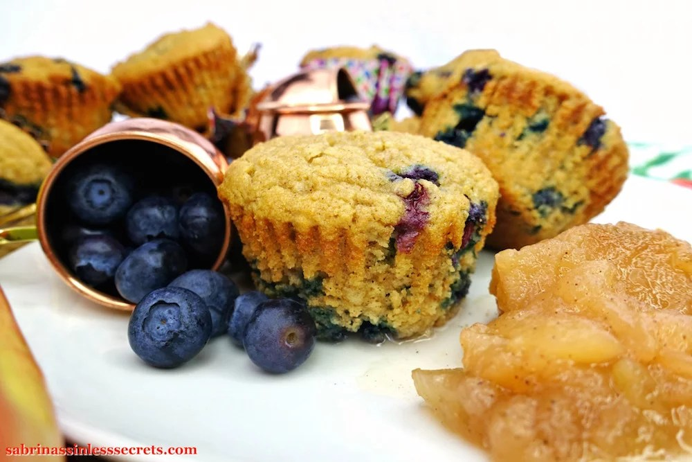 The side of an Apple Blueberry Paleo Muffin on a white plate with a side of homemade Paleo chunky applesauce and a poured over petite copper mug full of fresh blueberries with more muffins the background in various positions with an without liners on